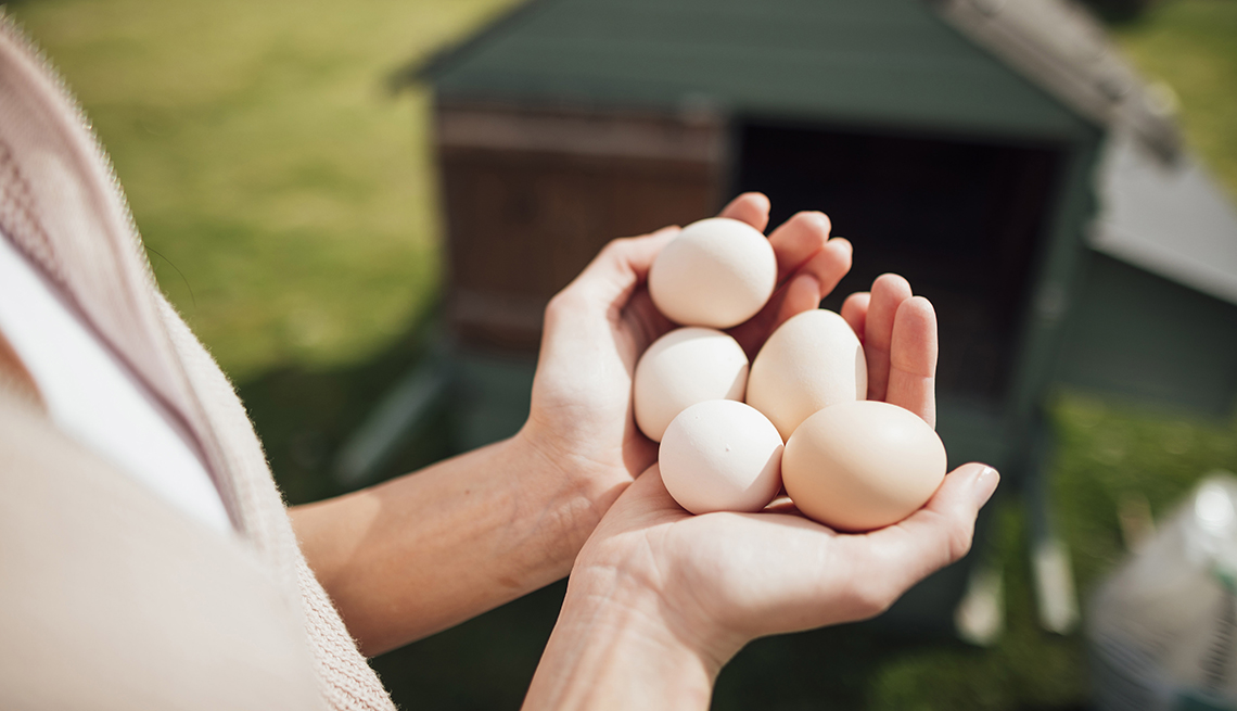 A pair of hands holding five fresh eggs