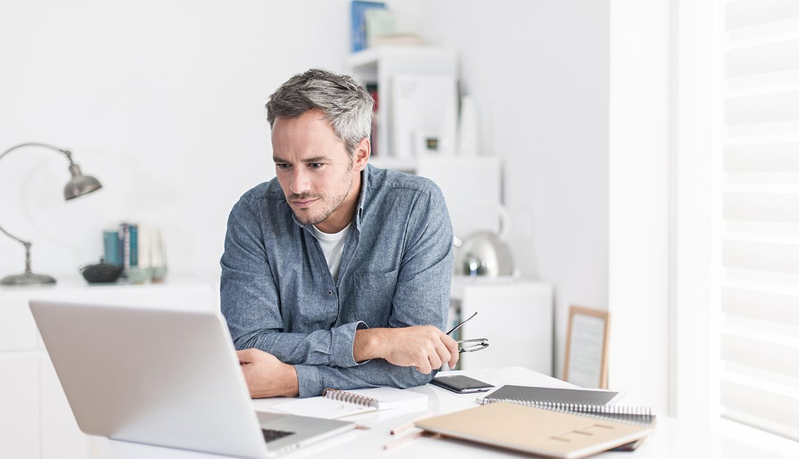 Imagen de un hombre sonriente que sostiene sus lentes mirando a su computadora portátil