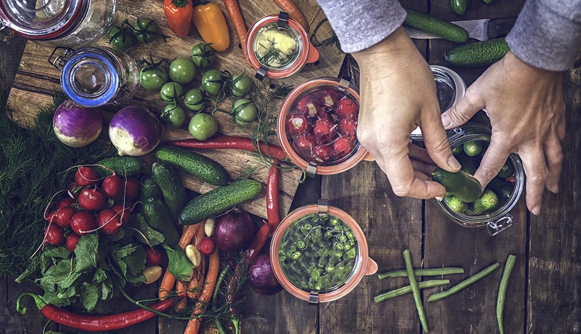 Surtido de verduras en una mesa de madera mientras una mano coloca los pepinos en un frasco