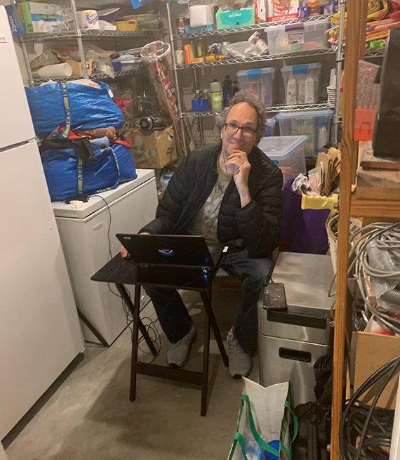 Un hombre sentado en su oficina en el sótano de su casa