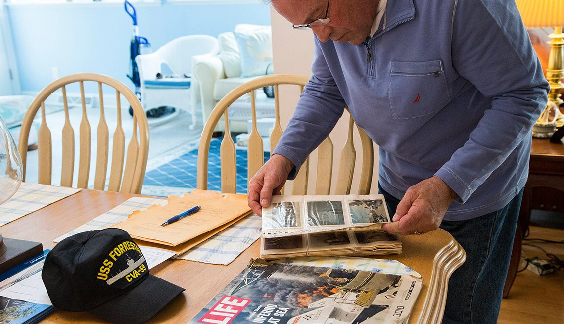 Sam Grenco is a Blue Water Navy Vietnam veteran looking through an old photo album on a table