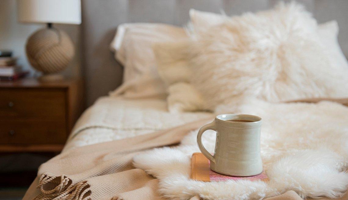 Taza de café y libro sobre una cama