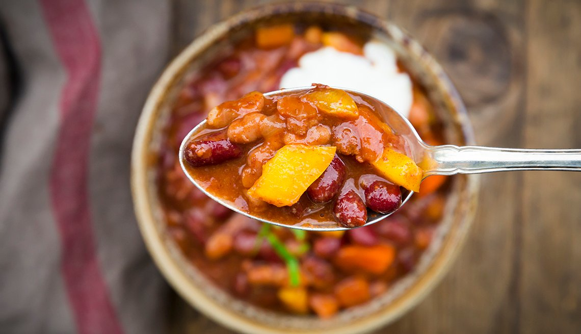 Chili con Carne with coriander and sour cream, spoon, close-up