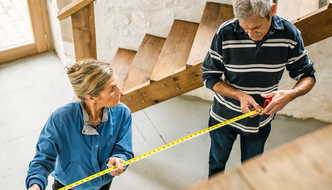 Couple doing DIY, using measuring tape