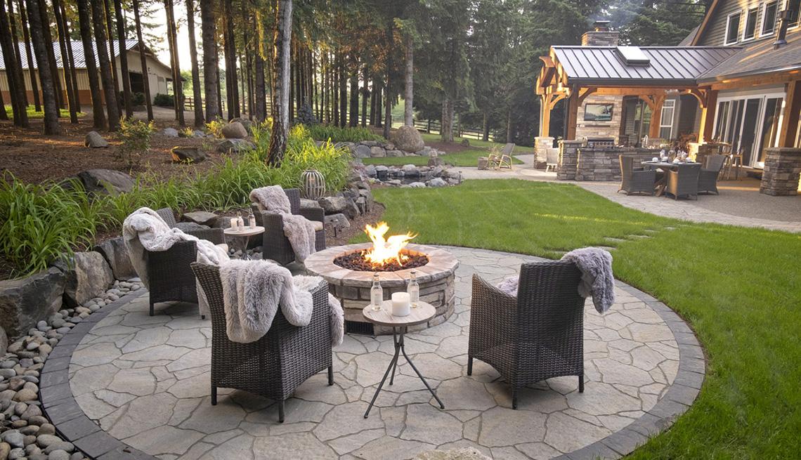 Un patio trasero con fogata, asientos al aire libre y mantas