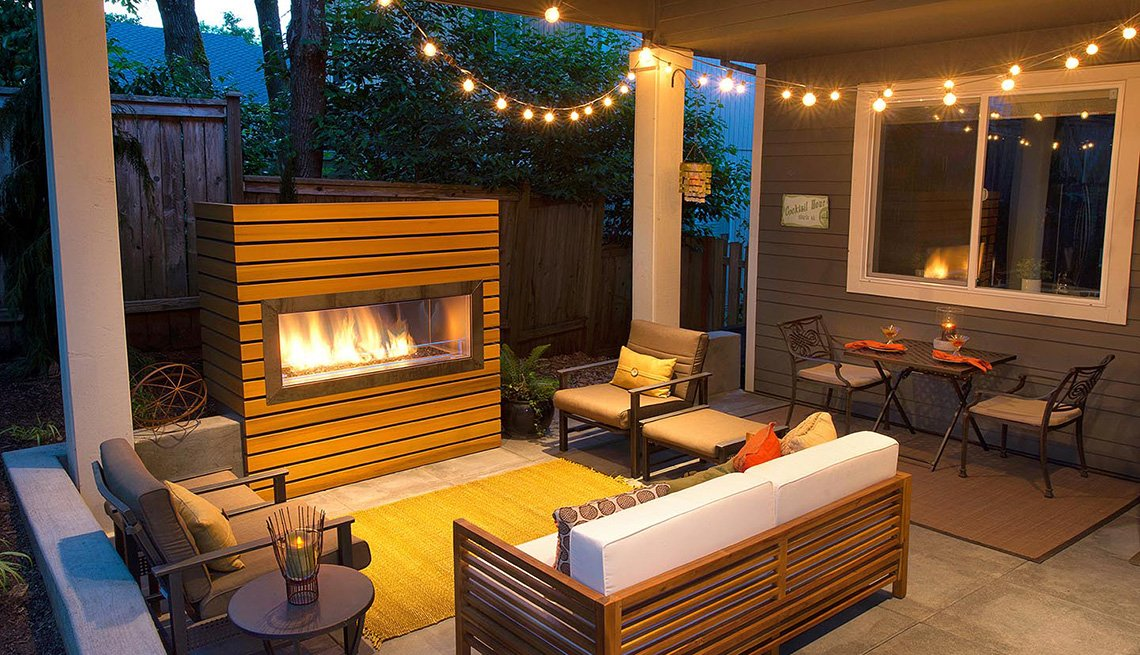 An outdoor patio with a fireplace and outdoor lighting