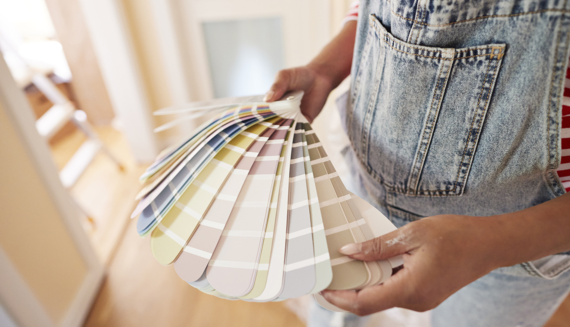 A woman choosing paint color from swatch at home