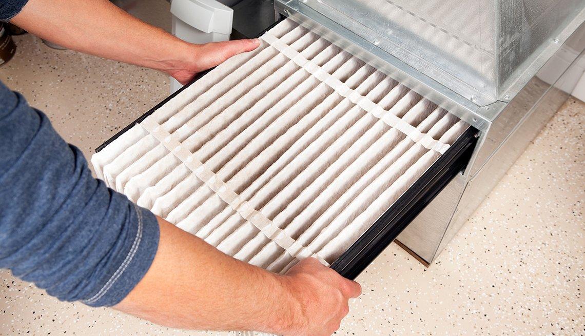 Persona revisa el filtro del aire acondicionado