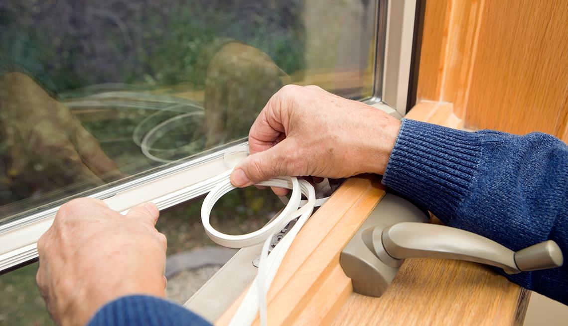 Persona sella los bordes de la ventana de una casa