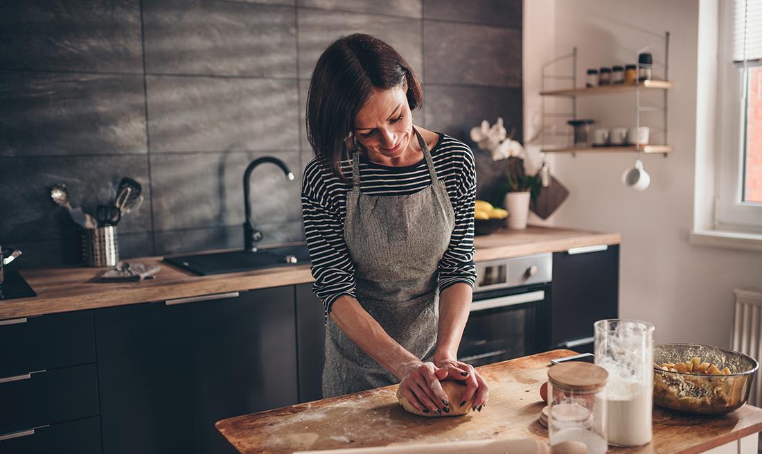 Mujer amasando la mezcla para un postre en la mesa de su cocina