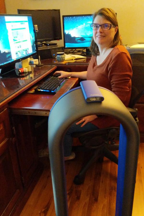Una mujer sentada en un escritorio junto a un filtro de aire