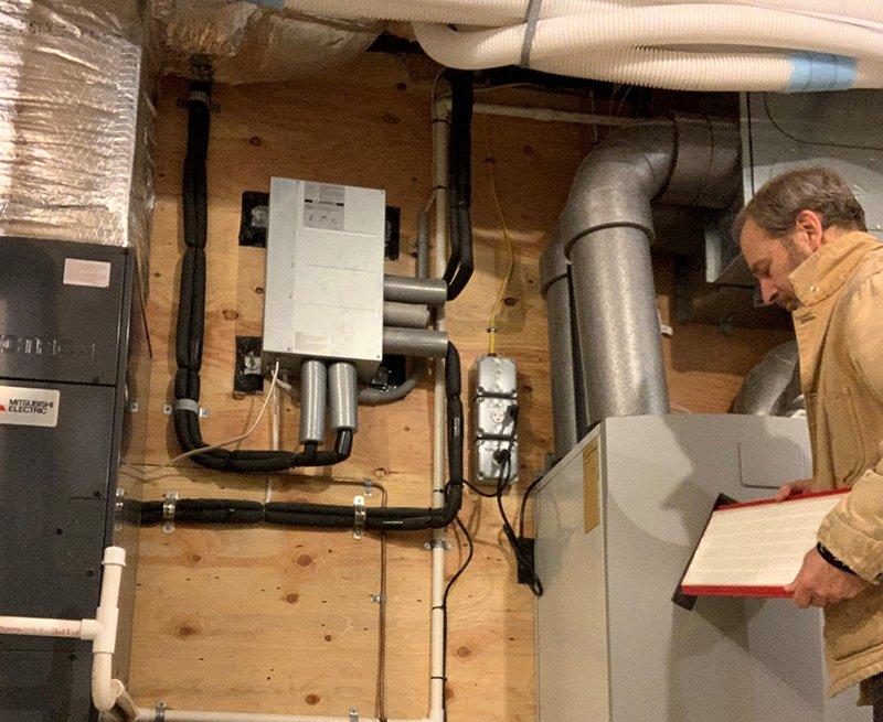 Un hombre comprueba su sistema de calefacción y refrigeración