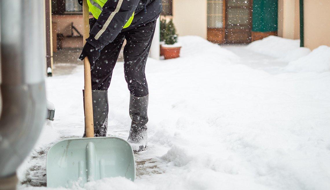 Persona quitando la nieve con una pala