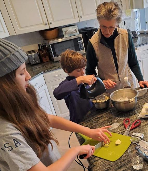 Abuela con sus nietos en una mesa de cocina mezclando masa para torta