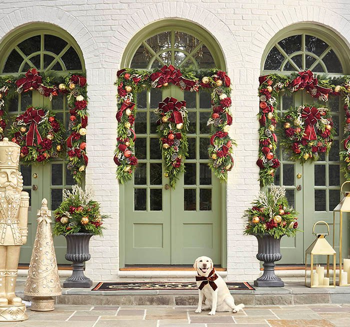 item 1 of Gallery image - Front door decorated in garland, with a dog smiling