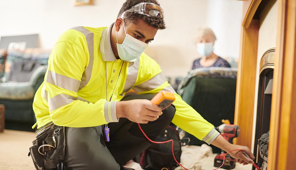 Un electricista trabaja en la sala de estar de una casa