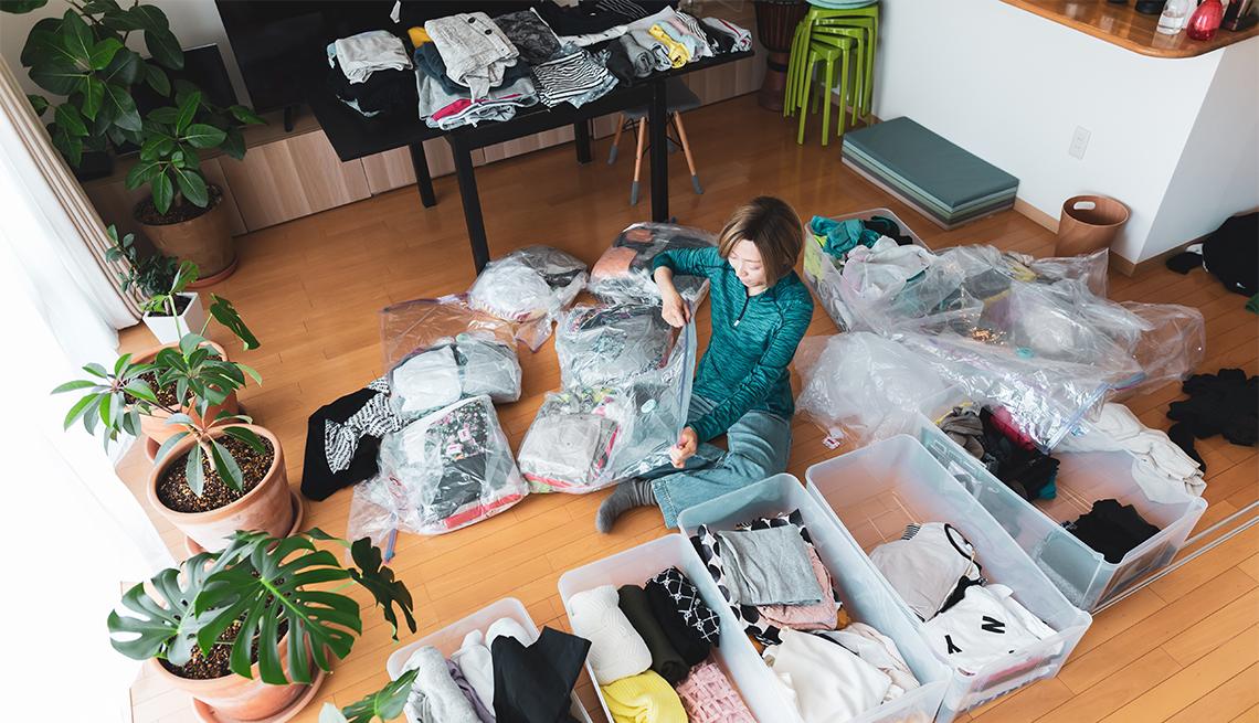 Una mujer organiza ropa en la sala de su casa