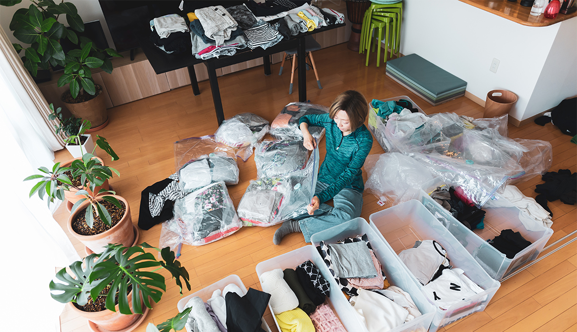 a woman organizes clothes in living room