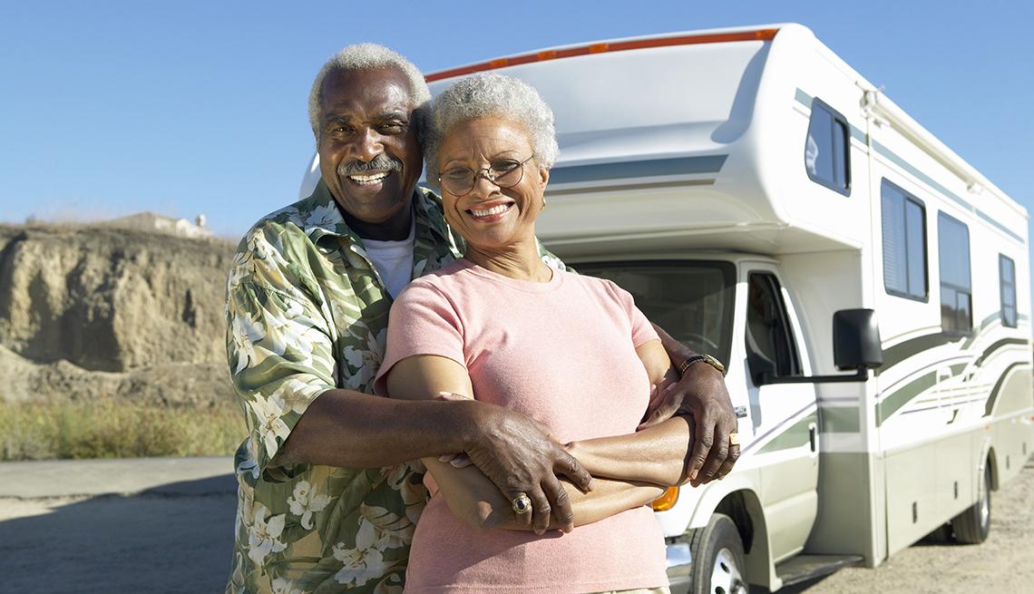 Una pareja feliz de pie frente a su vehículo recreativo o R V