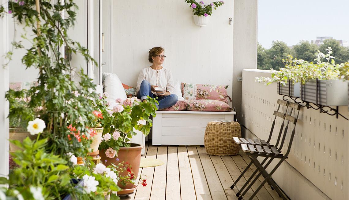 Mujer sentada en su balcón sonríe
