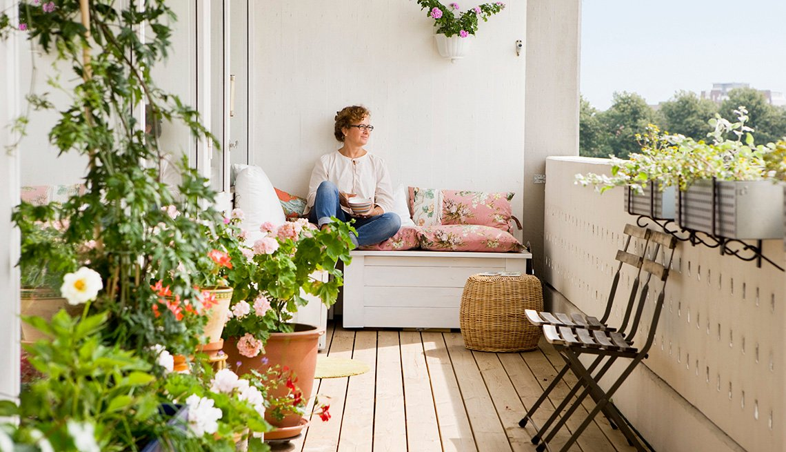 Woman sits smiling on her balcony