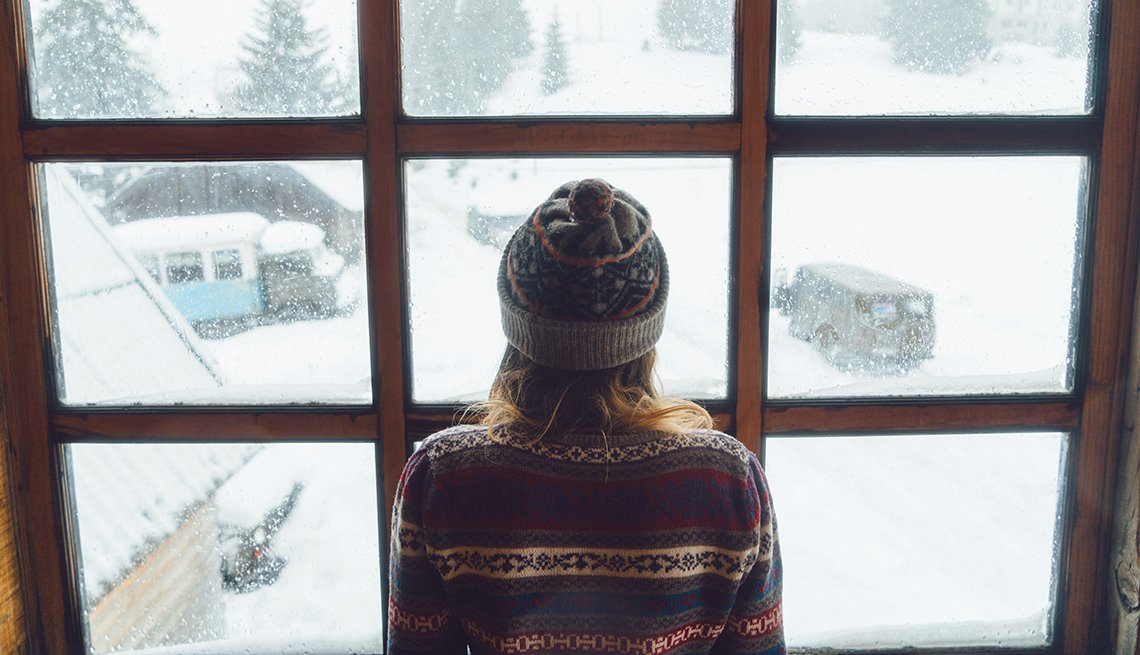 Mujer mira por la ventana en un día de invierno