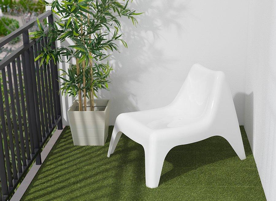 Una silla blanca sobre una grama sintética en un balcón