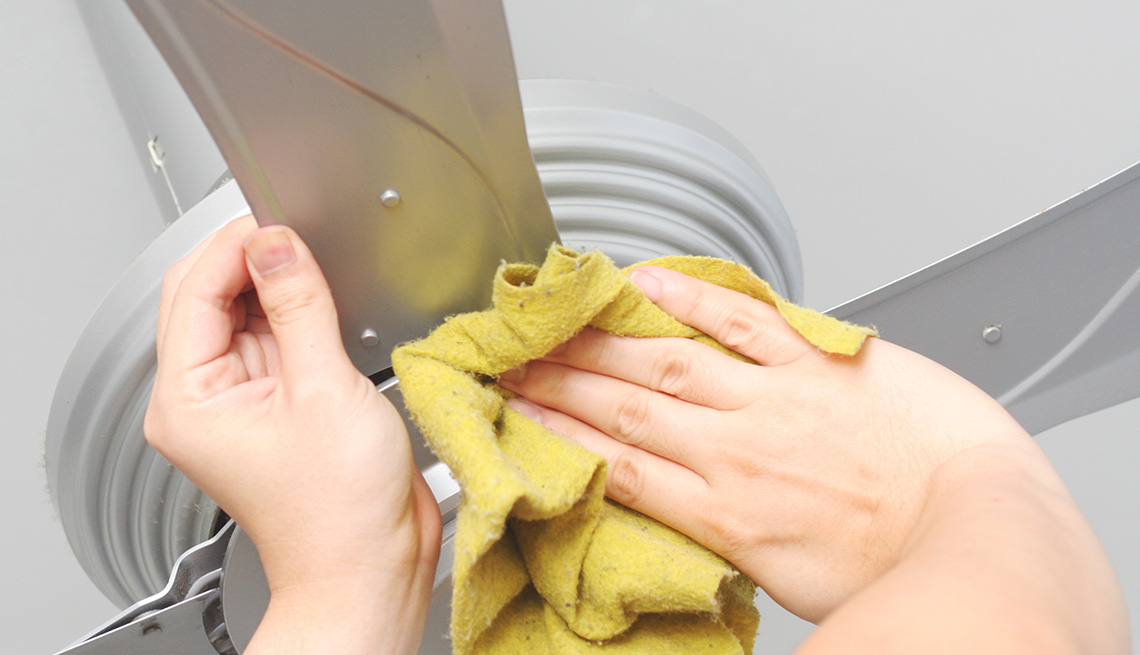Cleaning the ceiling fan with a wet yellow cloth