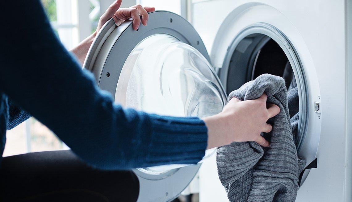 Mujer pone ropa dentro de la lavadora