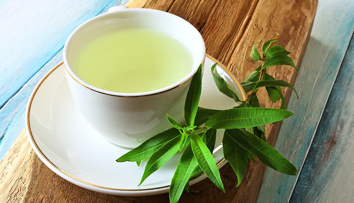 Hojas de limón junto a una taza de té