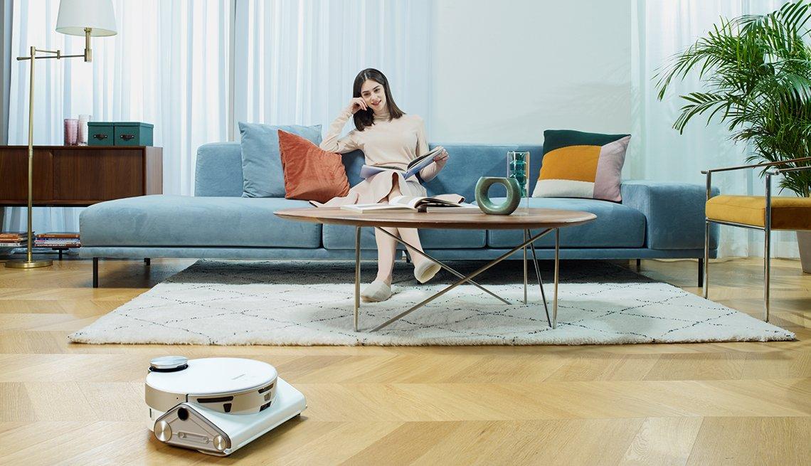 Mujer sentada en el sofá mira trabajar a la aspiradora Samsung JetBot 90