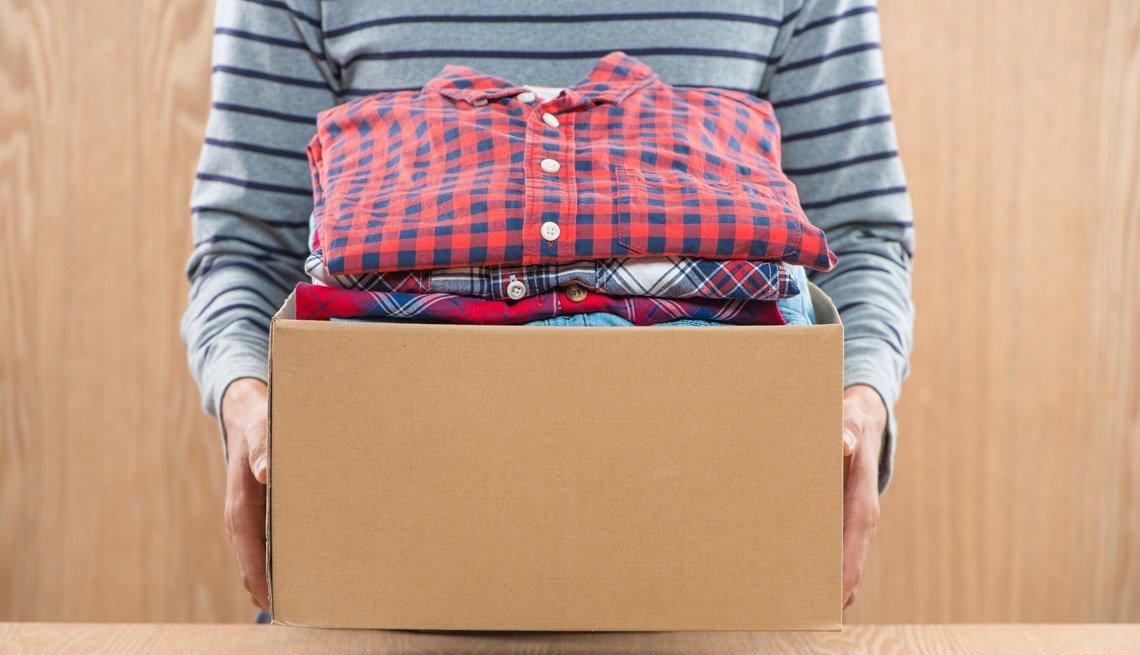Persona lleva una caja llena de ropa