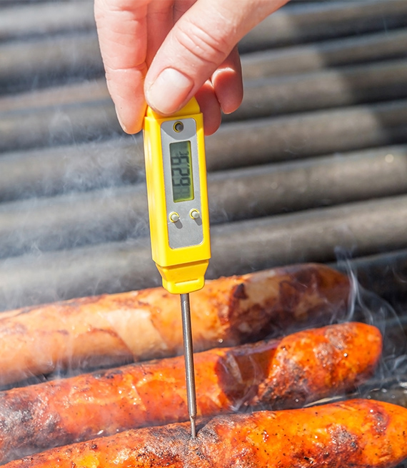 person checking sausages with a meat thermometer