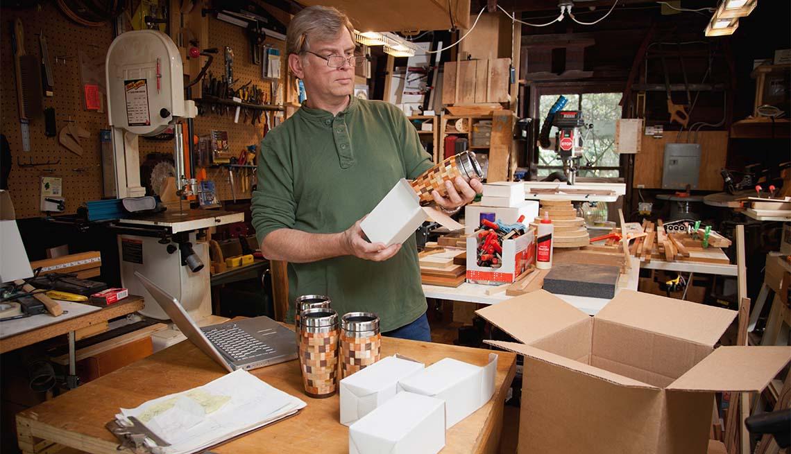 Hombre empaca tazas de madera artesanales en cajas de cartón