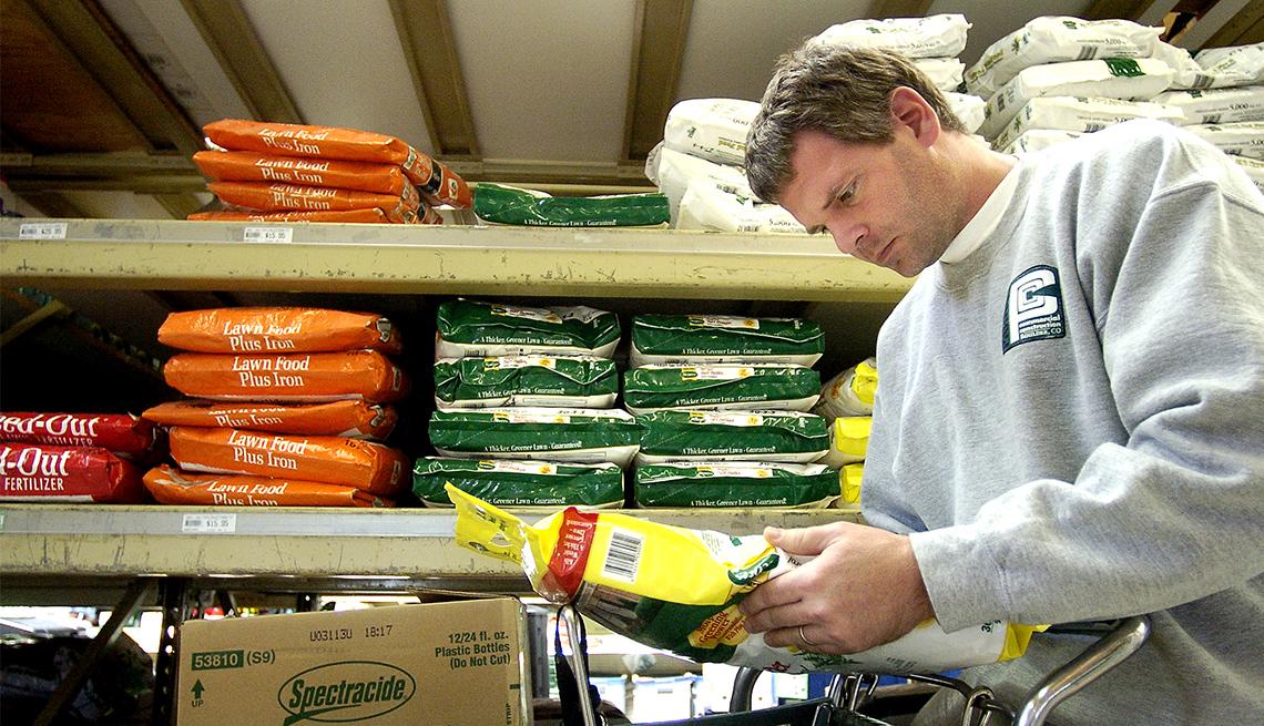 Hombre lee la información en la parte de atrás de una bolsa de fertilizante para césped