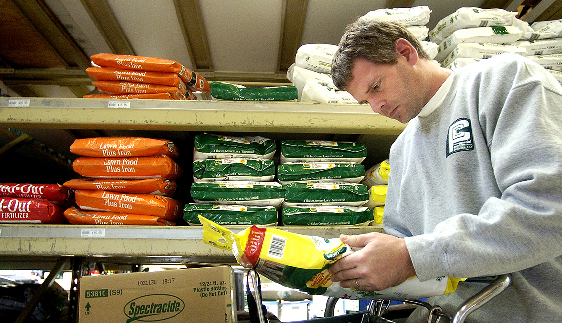 man reads information on the back of a bag of lawn fertilizer