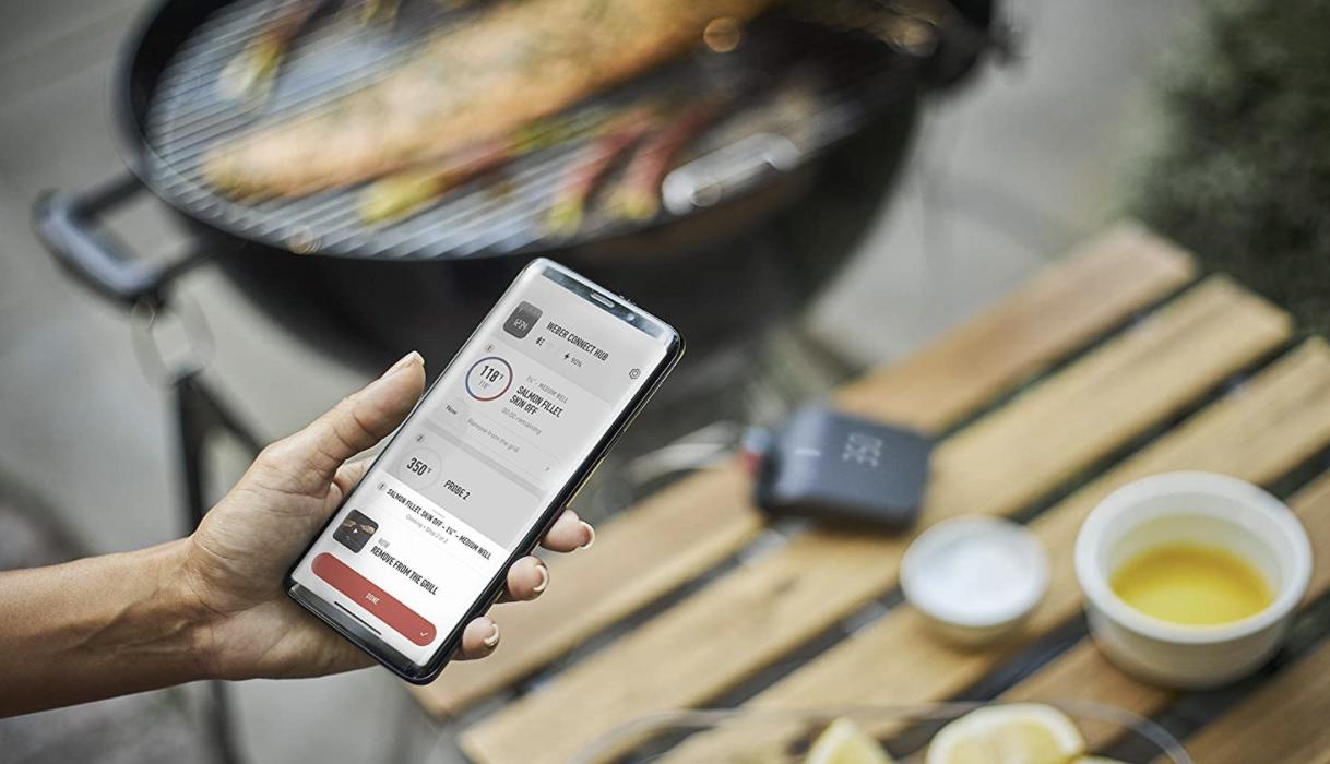 Mujer usa la aplicación Weber Connect en su teléfono