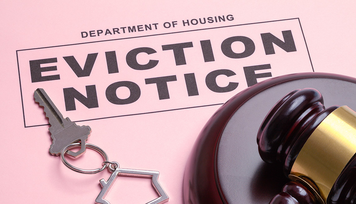 An eviction notice ruling printed on pink paper is displayed with a gavel and house keys