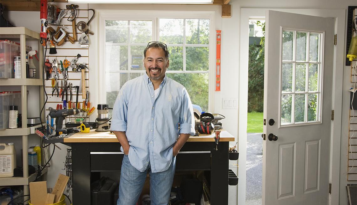man smiling in a garage workshop