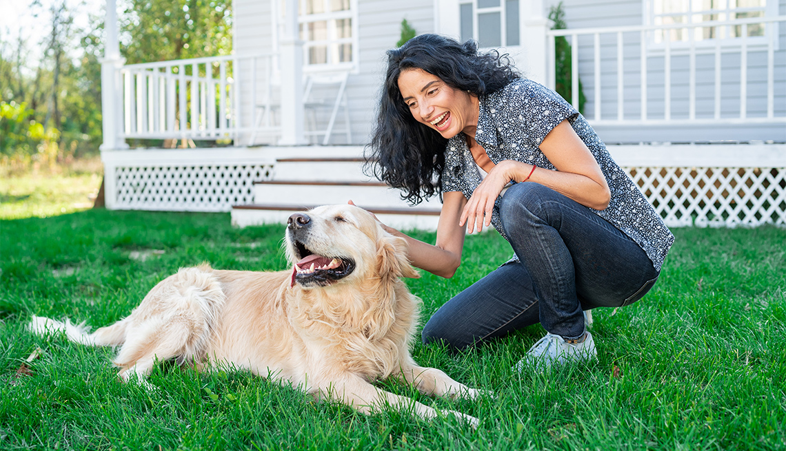 Smiling woman playing with her golden retriever on front yard