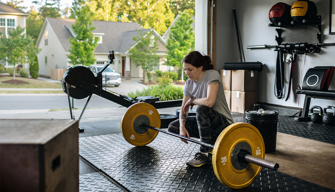 woman sitting in front of the barbell in her home garage gym