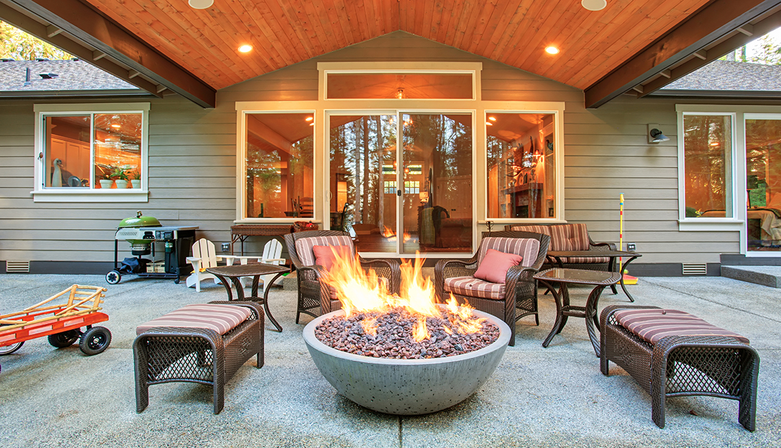 beautifully appointed firepit surrounded by benches and chairs in a back yard covered patio area
