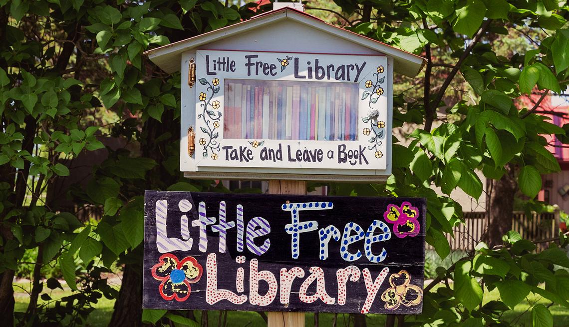Una casita pequeña llena de libros y letrero que dice Biblioteca gratis