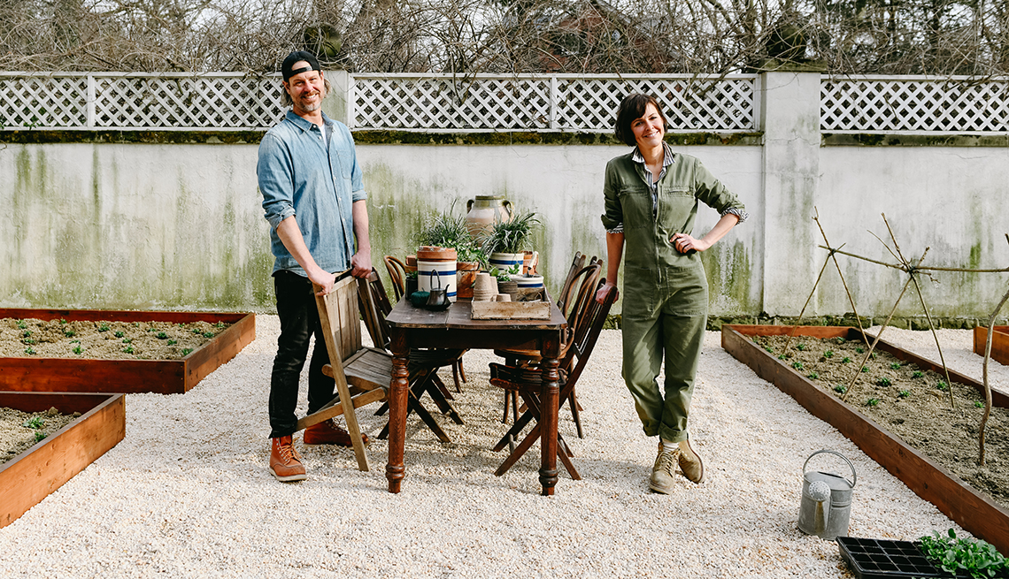 steve and leanne ford stand in a garden yard they designed