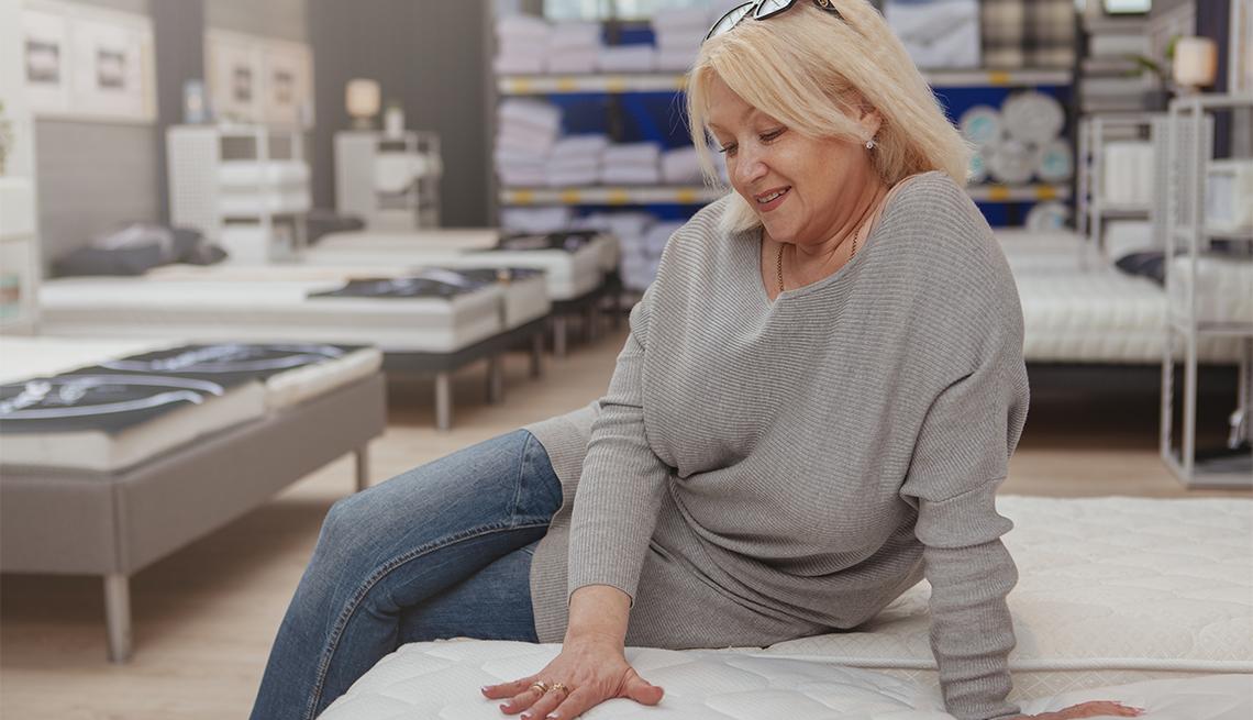 woman sitting on mattress at furniture store