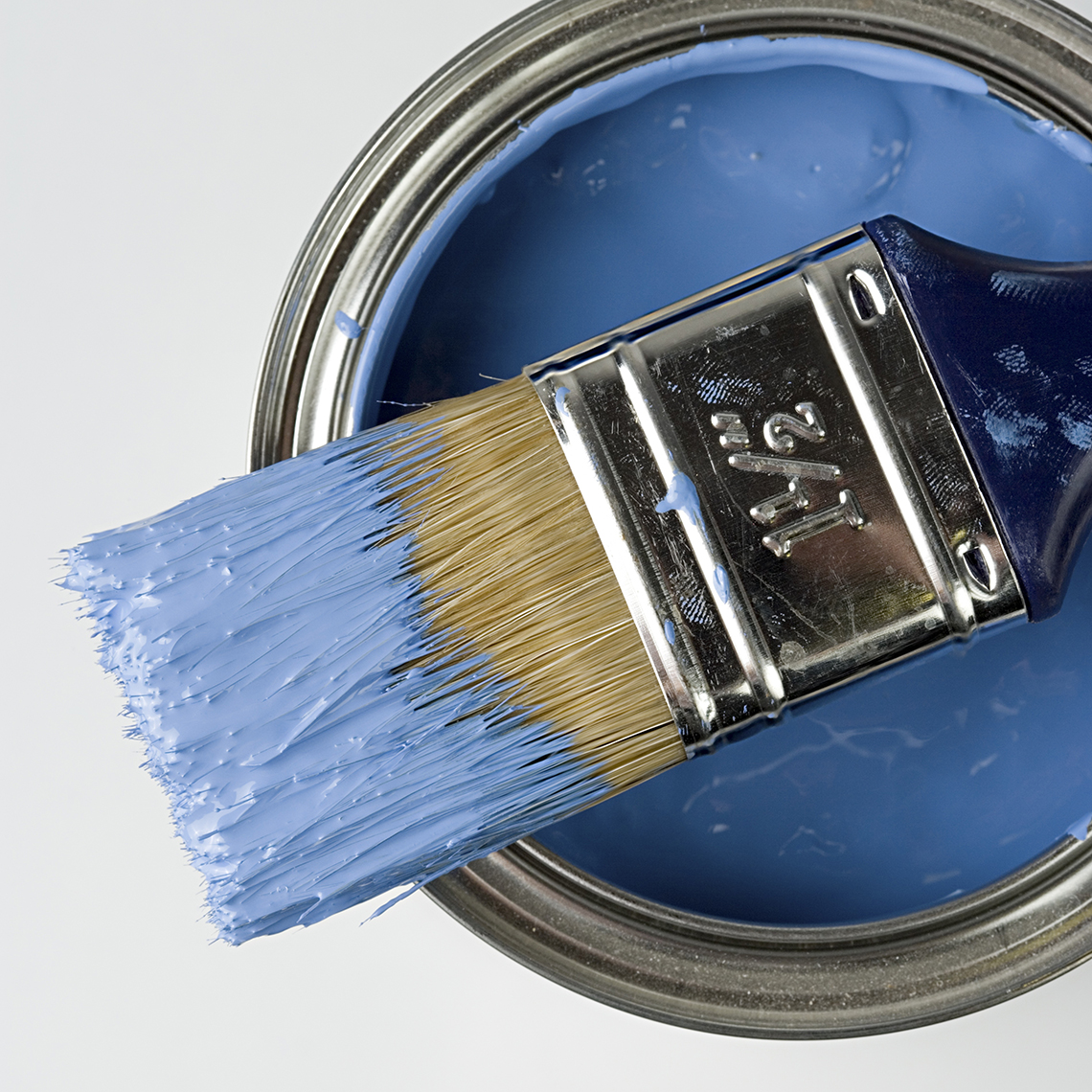 open can of blue paint with dopped brush laying atop it as seen from above
