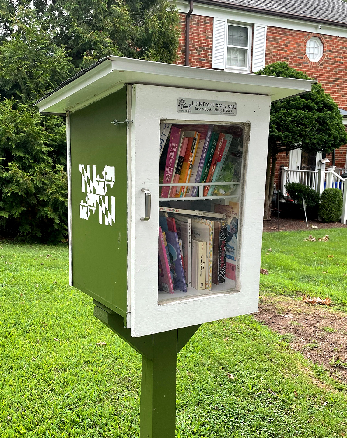 a little free library box and post in the front yard of a suburban home