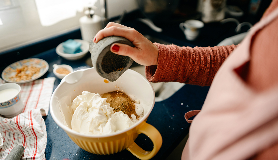 chef adds spices for a pumpkin cheesecake into a mixing bowl