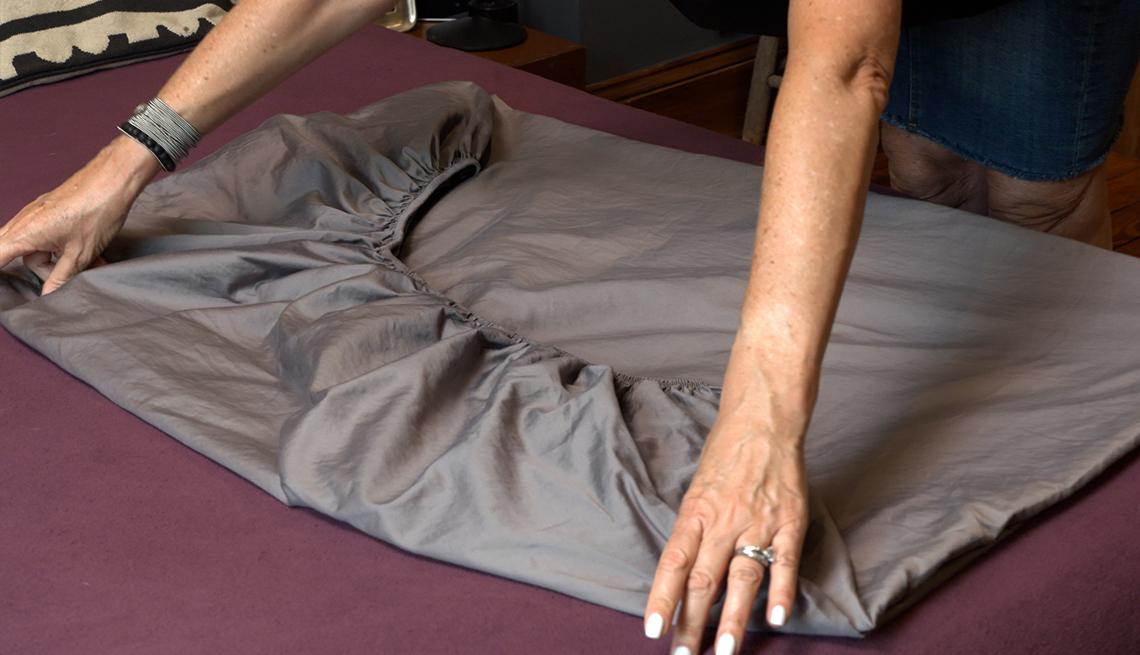 item 4 of Gallery image - Persona alisa los bordes de una sábana ajustable parcialmente plegada
