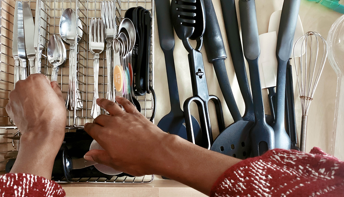 hands organizing cutlery in a kitchen drawer